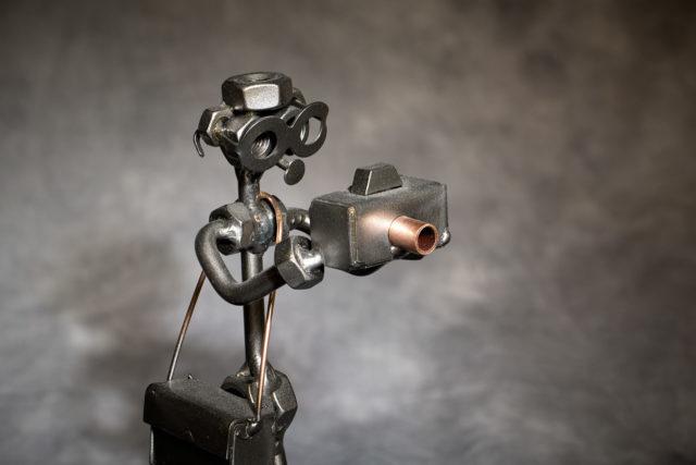 Fotograf aus Schrauben u. Metall zusammengeschweißt